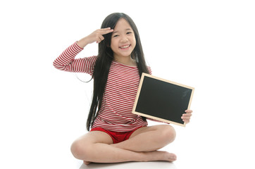 Little beautiful asian girl sitting and holding chalk board