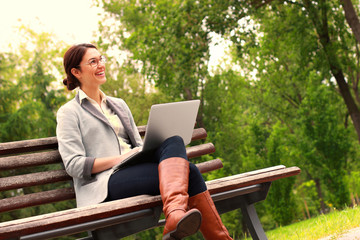 Woman with laptop in park smiling