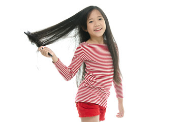 Little asian girl smiling and brushing hair