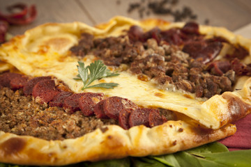 Turkish meal pizza pide stuffed with meat, cheese, pastirma