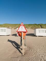 Rettungsring am Strand vor weissen Häusern