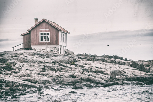 Red wooden house at sea shore in vintage or retro style, - 72079600