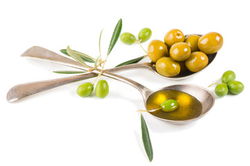 fresh olive oil and olives in a two spoons