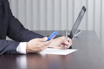 businessman writing and holding smart phone