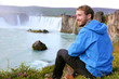 Iceland tourist relaxing by waterfall Godafoss