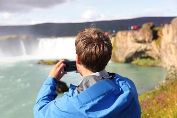 Tourist taking photo of waterfall Godafoss Iceland