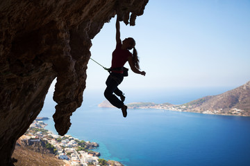 Silhouette of a young female rock climber on a cliff