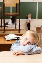 Sad schoolboy in classroom