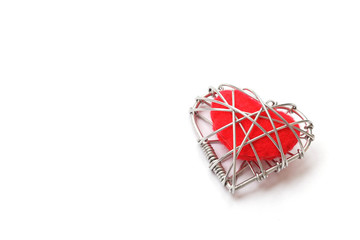 red fabric heart in wire on white background