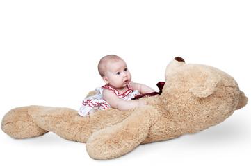 little girl plays a huge teddy bear