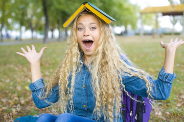 Cheerful girl student with a book on his head