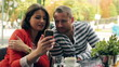 Couple watching something funny on smartphone, steadycam shot