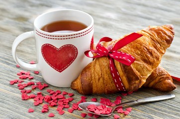 Cup of tea with croissants heart shape decoration on wooden back