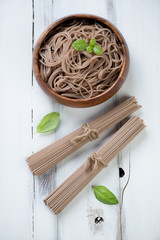Soba noodles with green basil over white wooden background