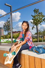 Beautiful girl holds skateboard and sits on side