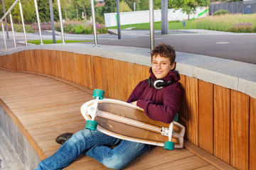 Boy with headphones relaxes and holds skateboard