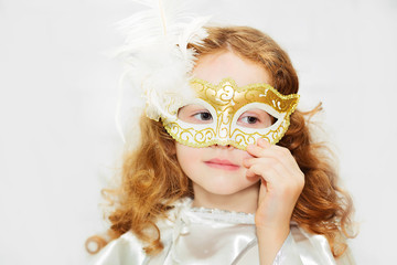 Portrait of а curly little girl in venetian mask on a light bac