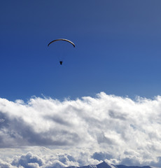 Silhouette of paraglider and blue sun sky