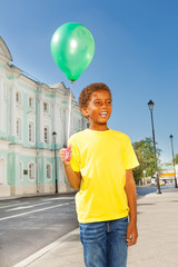 Positive African boy with green flying balloon