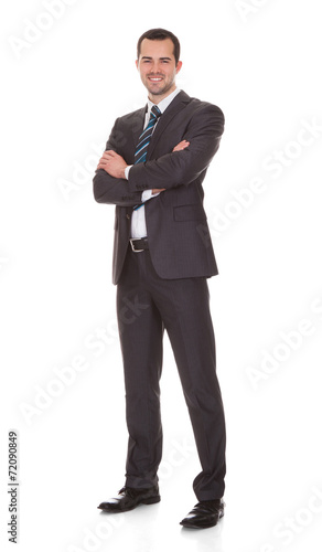 canvas print picture Confident Young Businessman Standing Arms Crossed