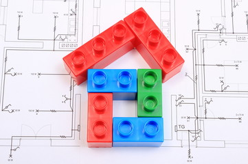 House of colorful building blocks on drawing of home