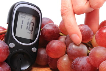 Fresh natural grapes and glucometer in background