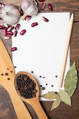paper for recipes and spices on wooden table