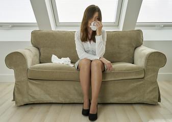 Frau auf Couch mit Taschentüchern