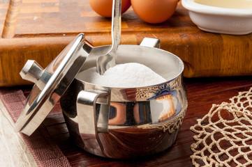 Zuccheriera di acciaio contenente zucchero su tavolo