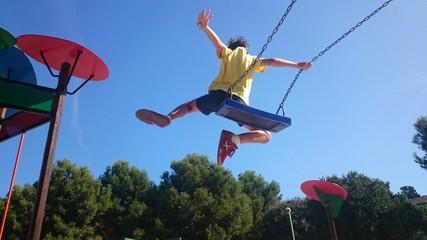 Niño saltando de columpio