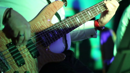 musician playing bass guitar in a disco lights