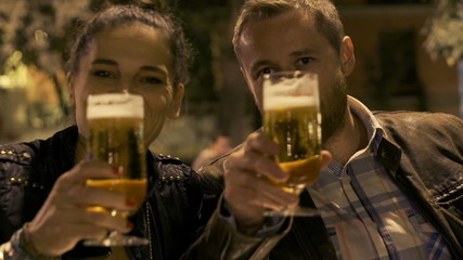Couple cheers to the camera and drinking beer, steadycam shot