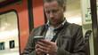 Man tweeting on the phone in metro, steadycam shot