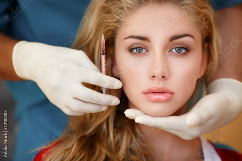 Fototapeta Cosmetologist holding syringe and woman's face in hands