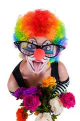 clown  with a bouquet of flowers puts out the tongue looks up