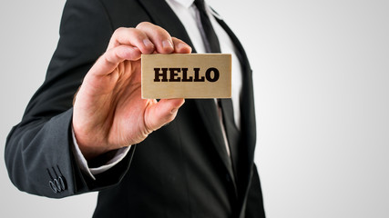 Businessman holding a wooden sign saying Hello