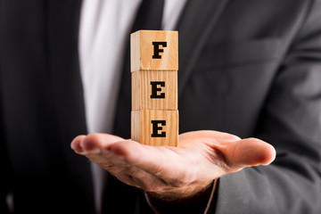 Businessman holding wooden blocks reading Fee