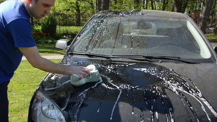 Young man manual clean wash car hood with sponge in garden
