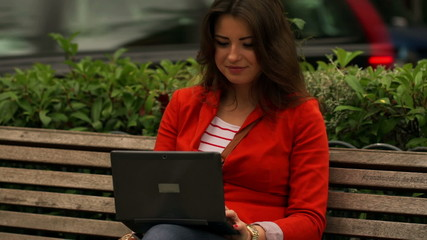 Woman sitting on the street bench and working, steadycam shot