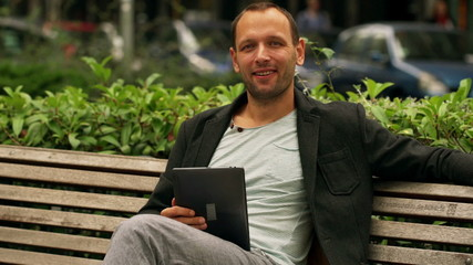 Happy man using tablet and smiling to the camera on bench