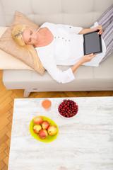 Reife Frau mit Tablet Pc und Kirschen auf dem Sofa