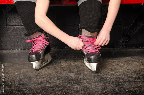Keuken foto achterwand Wintersporten A Girl Tying Ice Hockey Skates in Dressing Room
