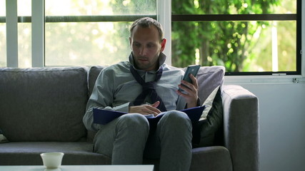 Businessman working on papers and using cellphone at home