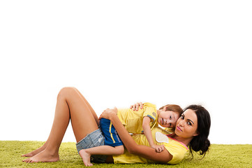 young mother hugging her son lying on the the green grass
