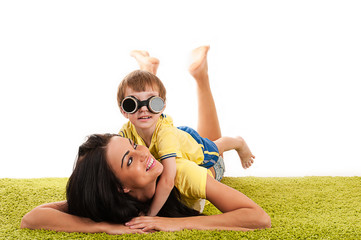 happy mother and son playing on green grass