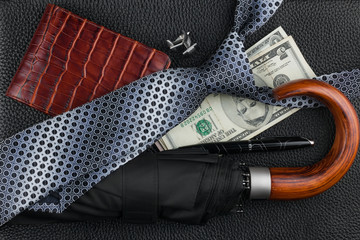 Tie, umbrella, pen, wallet, cufflinks, money lying on the skin
