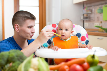 young dad feeding his baby at kitchen