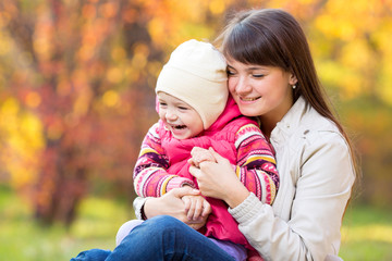 happy young mother and her daughter have fun sitting at autumn b