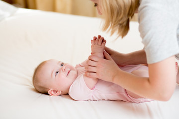 mother massaging or doing gymnastics baby girl