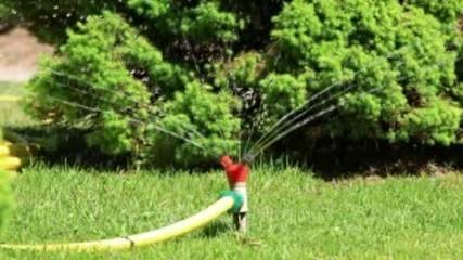 Sprinklers spraying water on green grass